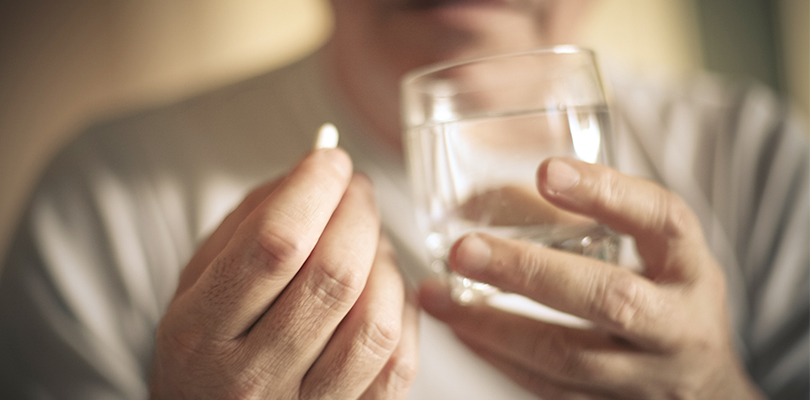 Man about to take medication with glass of water