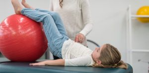 Young girl using exercise ball with physical therapist