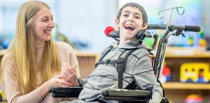 A young boy in a wheelchair with a woman.