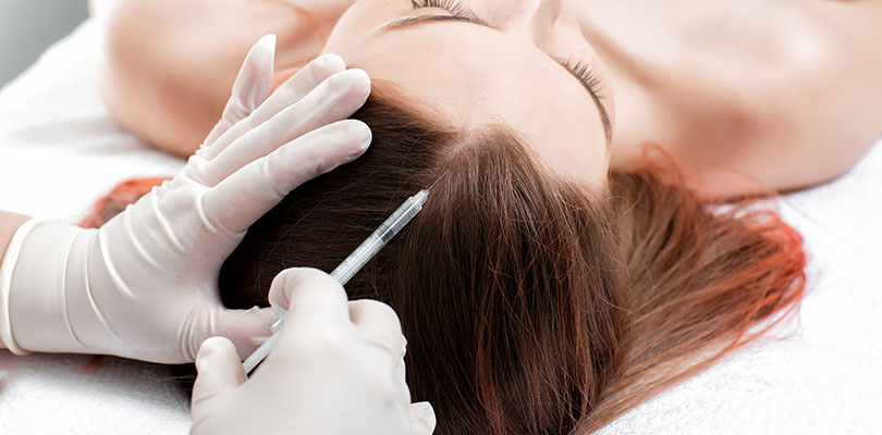 A woman is receiving a hair loss treatment procedure