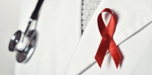 A doctor is wearing a HIV/AIDS ribbon