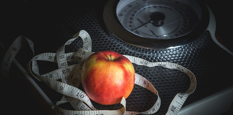 A weight scale, apple, and body measuring tape