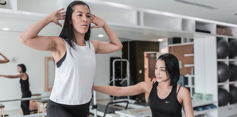 Woman is being coached by a personal trainer