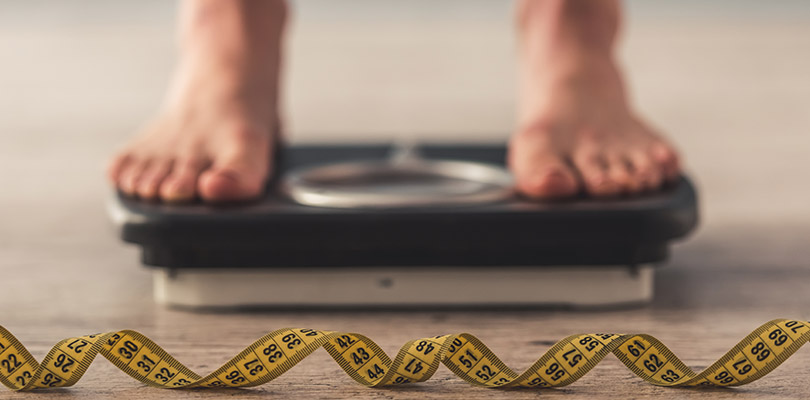 Image of woman feet standing on weigh scales, a tape measure in the foreground.