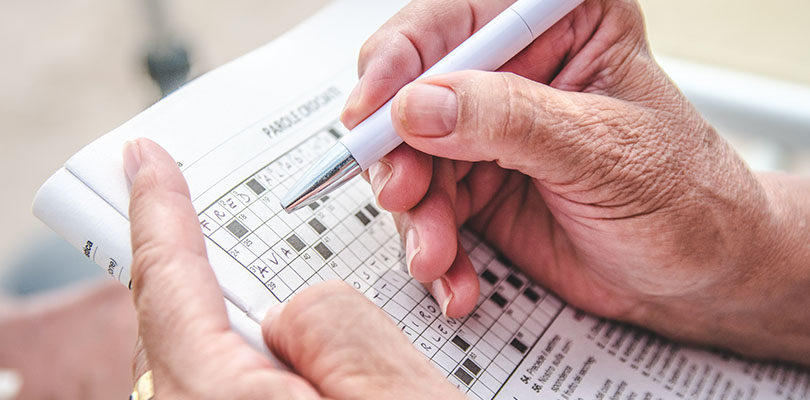 Elderly person completing a crossword puzzle.