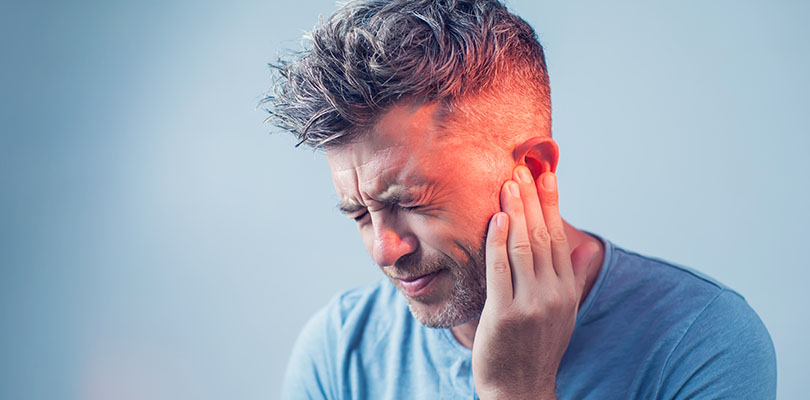 A man is experiencing ear pain or an earache