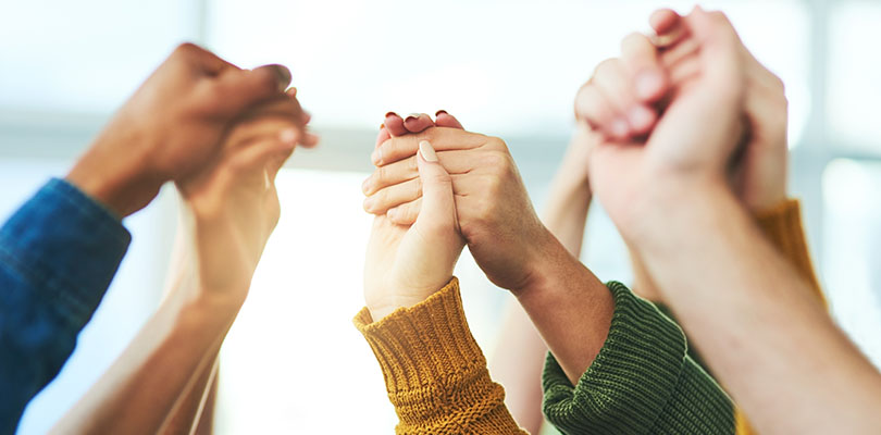 Closeup shot of a diverse group of people holding hands together in unity