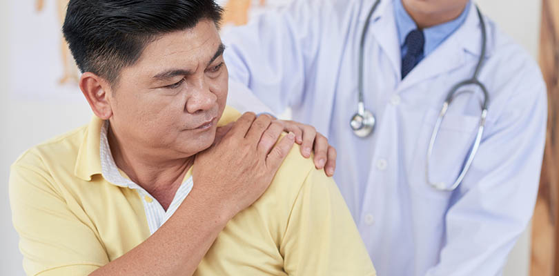 Senior Asian man visiting doctor as he is suffering from pain in shoulder