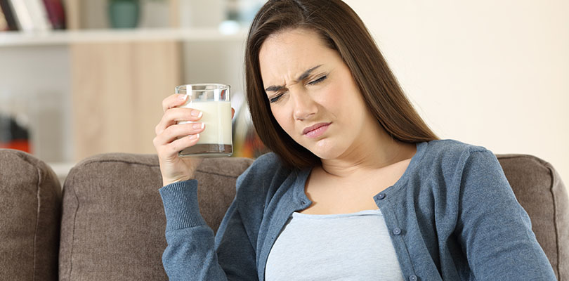 Woman suffering lactose intolerance sitting on a couch in the living room at home