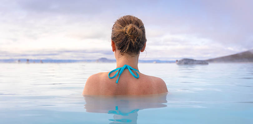 Geothermal spa in Iceland with young woman enjoying bathing in hot thermal pool with hotspring water for wellness and skin treatment, icelandic experience