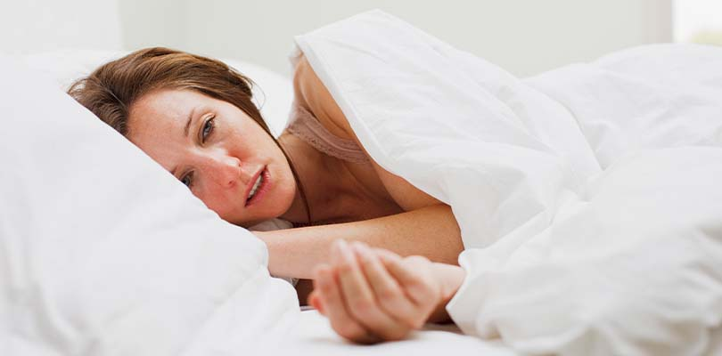 A woman in white sheets sweating.