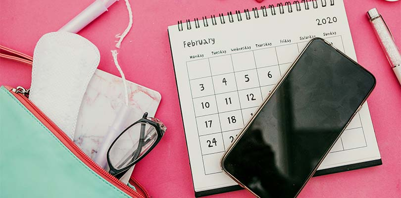 Period supplies, a calendar and a phone against a pink background.