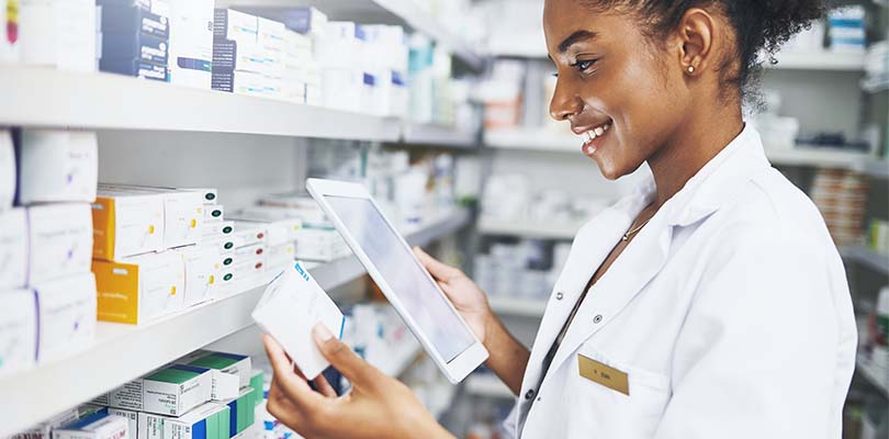 A pharmacist looking at medicine and a tablet.